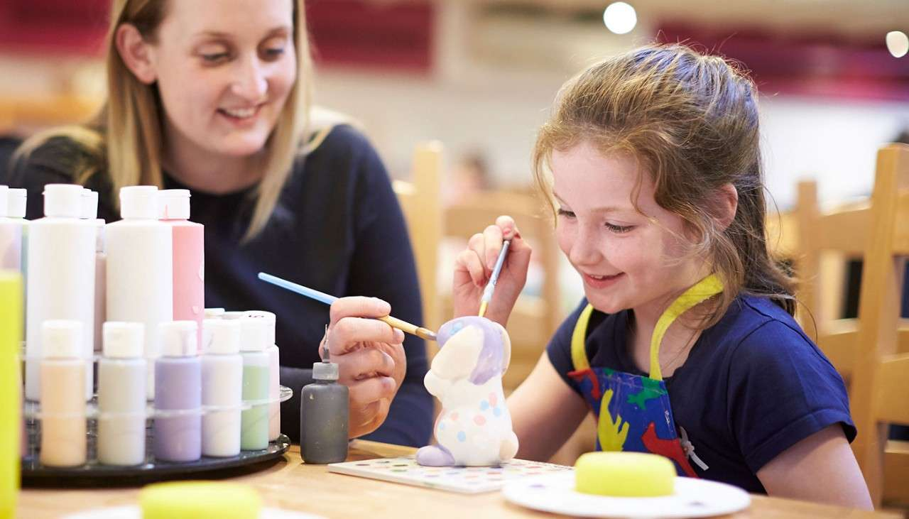 Parents give their daughters shoulder rides down a path lined with daffodils