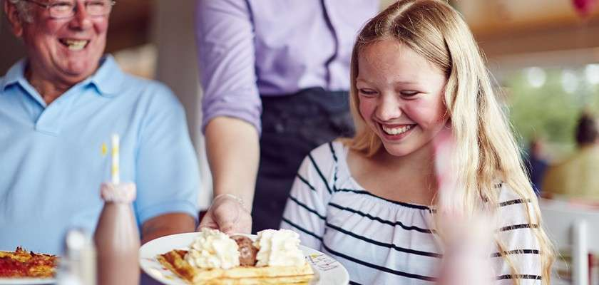 Waitress placing a plate of waffles on the table for teenage girl