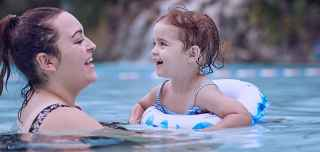 Mother playing with her daughter who is in a rubber ring in the Subtropical Swimming Paradise