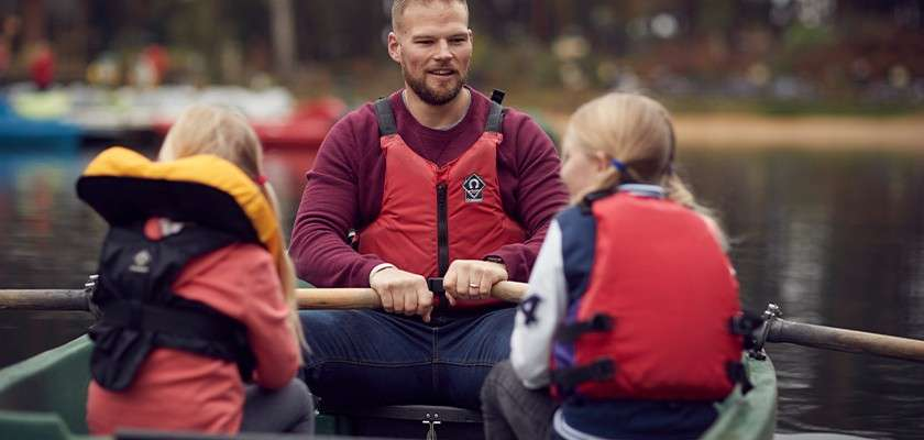 Father with two daughters in a rowing boat on a Center Parcs lake