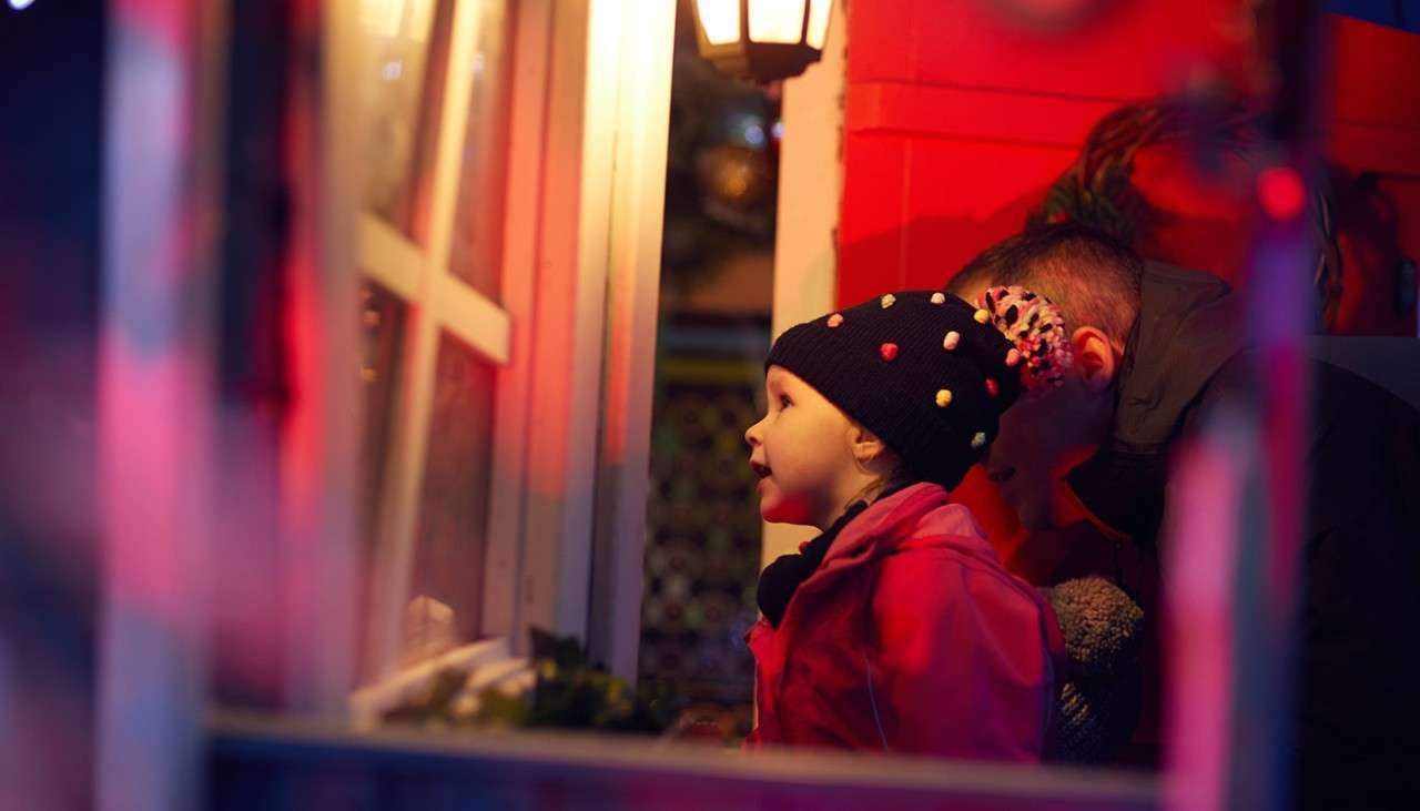 Walkway with twinkling lights, and snow covered floors. Decorated cabins containing festive scenes line your path.