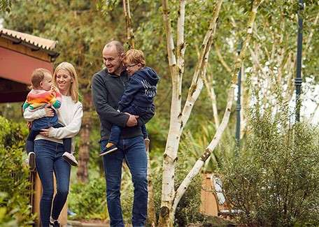 Mum carrying young daughter and Dad carrying young son through the Center Parcs village