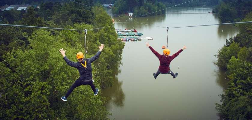 Two people on zip line over the lake on Aerial Adventure activity