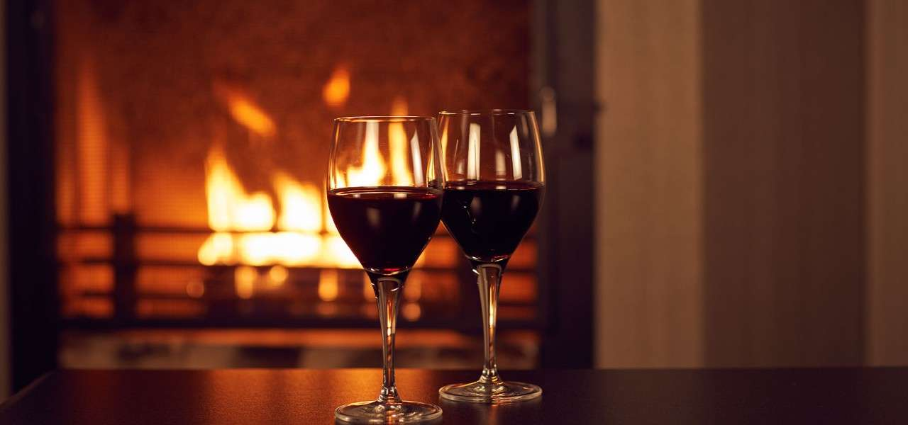 Two glasses of wine in front of an open fire in a Center Parcs lodge