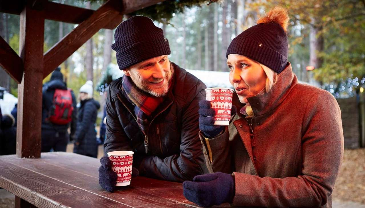 Man and woman wrapped up in hats and gloves sat on a picnic table holding hot drinks at Winter Wonderland