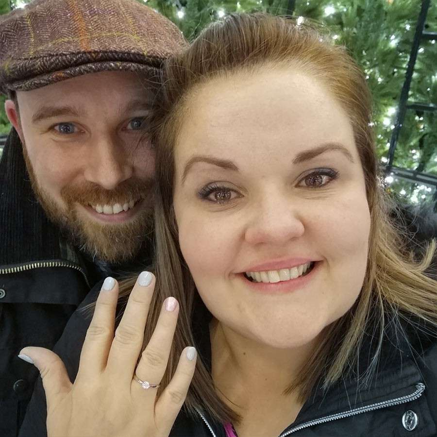Woman showing off her engagement ring in a selfie with her partner