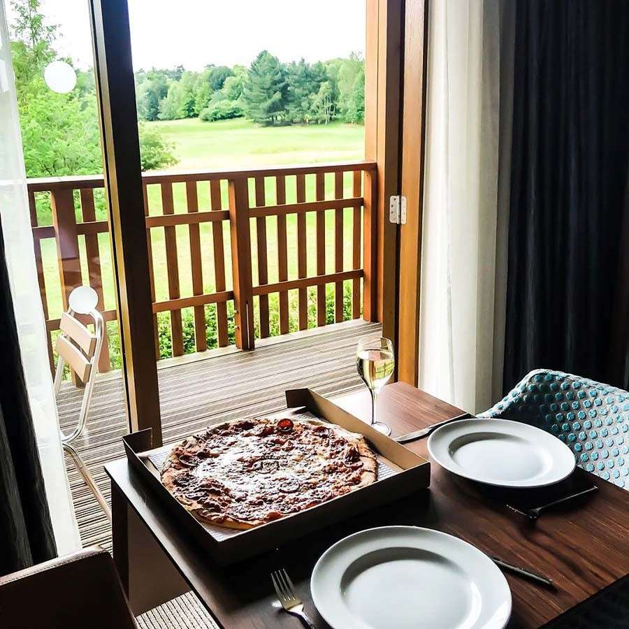 Table set up with pizza and wine in a Center Parcs apartment, showing a beautiful forest view from the balcony