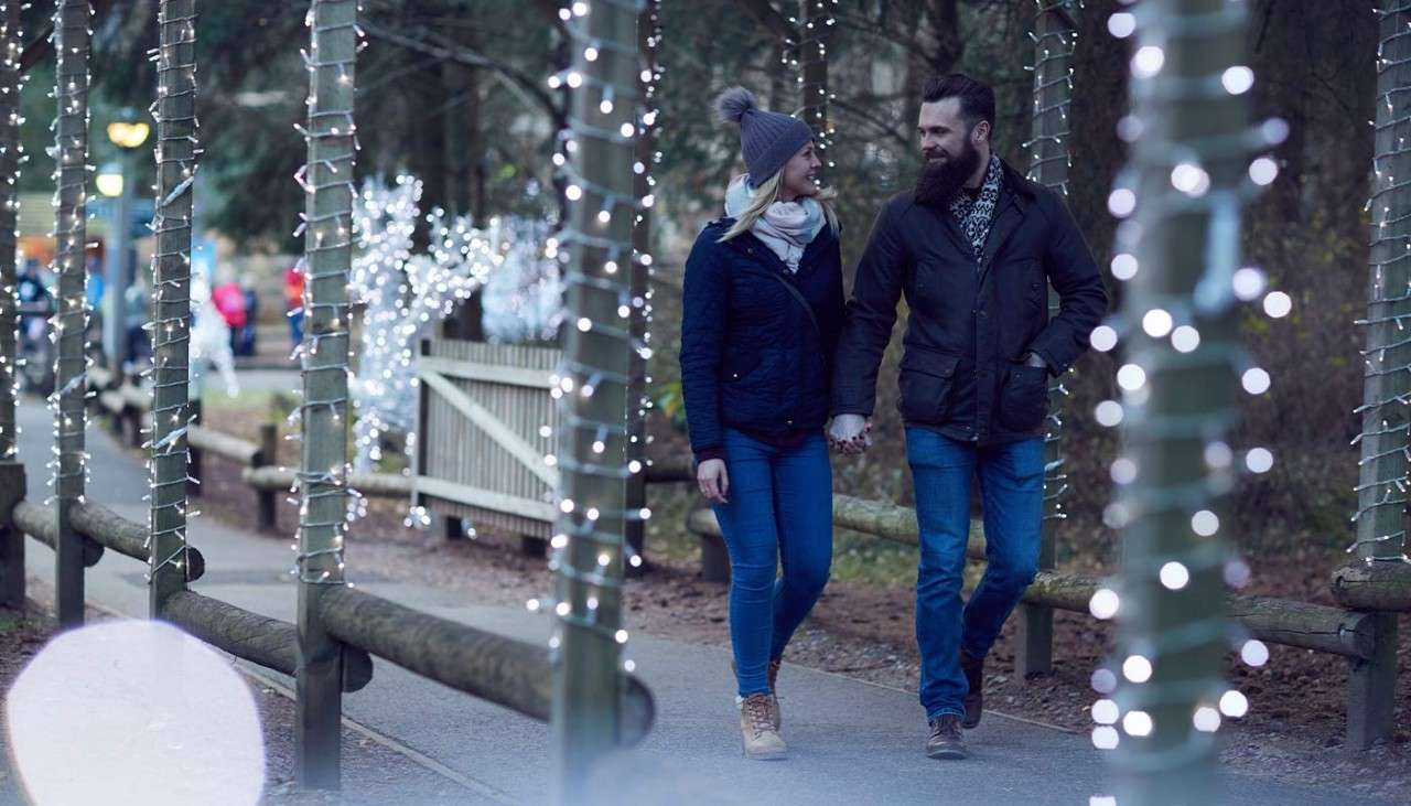 Couple holding hands as they walk through Winter Wonderland where the pathway is decorated with Christmas lights