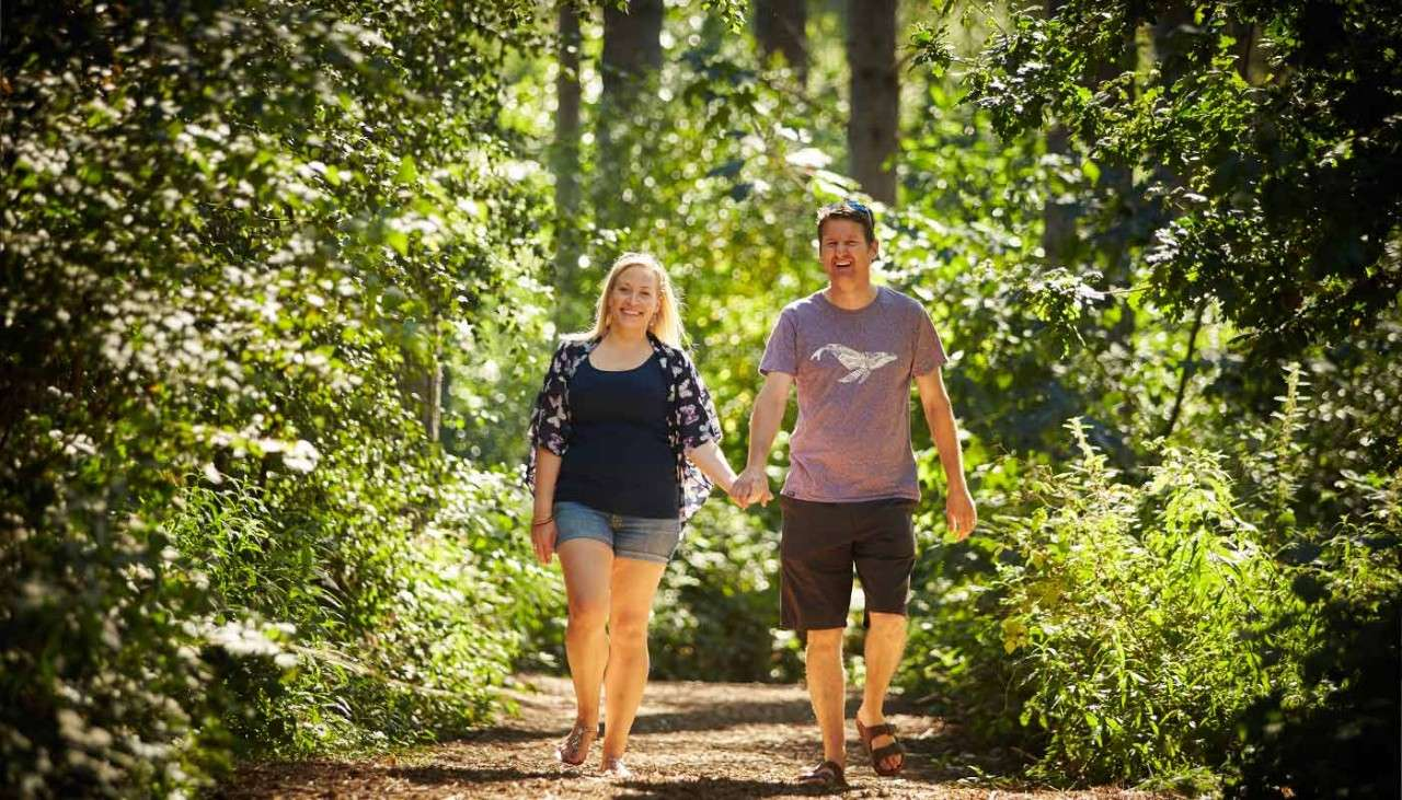 Man and woman walking through the forest on a summers day