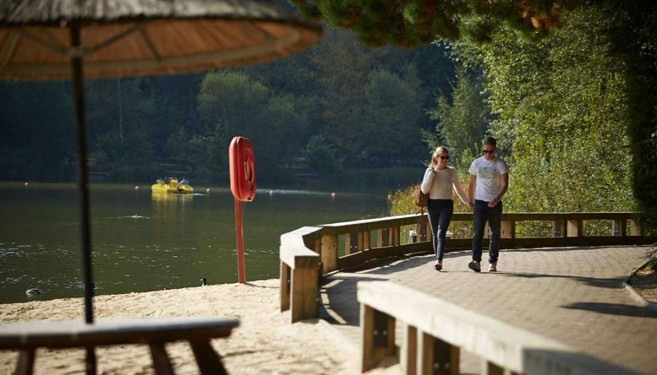 Man and woman walking along a path beside a Center Parcs lake and the beach