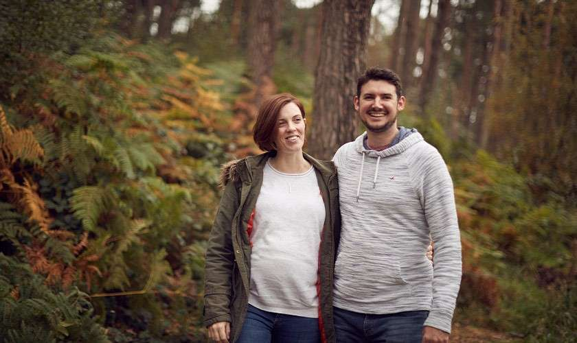 Man and pregnant partner walking through the forest
