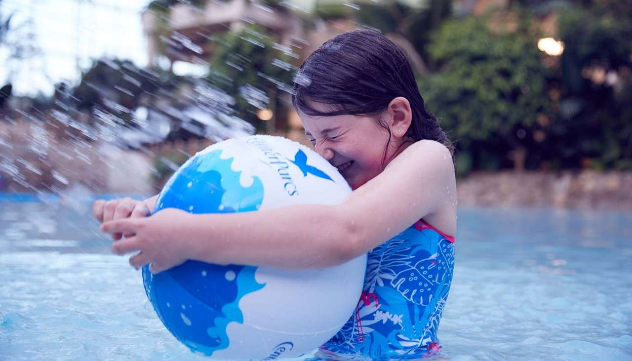 Girl with beach ball in pool