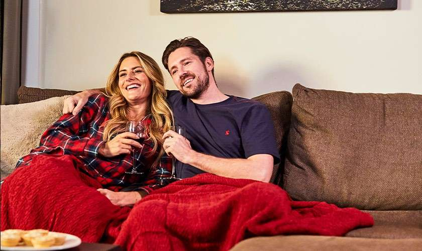 Couple enjoying glasses of wine while wrapped in a blanket on a sofa in their lodge