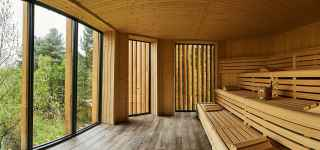 Wooden Nordic sauna looking out into the woodland scenery.