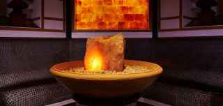 Japanese Salt Steam Room, large rose quartz in a stone bowl with a glowing back wall.