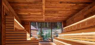Wooden sauna with benches and wooden bucket.