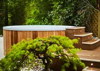 Outdoor hot tub in a beautiful woodland scenery.