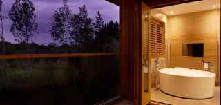 Luxury Spa Break circular bath tub looking out onto a purple clouded forest view.