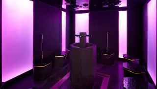 Mineral steam room with tall pillars bathed in purple light.