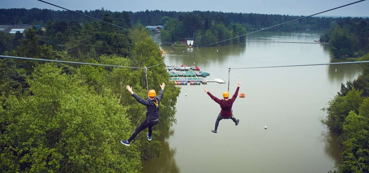 Two people going down the double zip wire over the lake