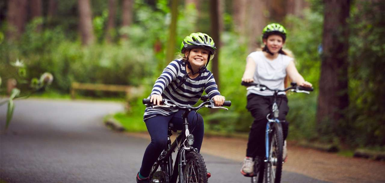 Two girls cycling through the forest on hired Center Parcs cycles