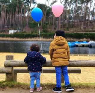 Two children with balloons next to the beach