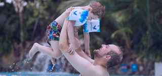 Father lifting his son in the pool. The boy wears Center Parcs arm bands.