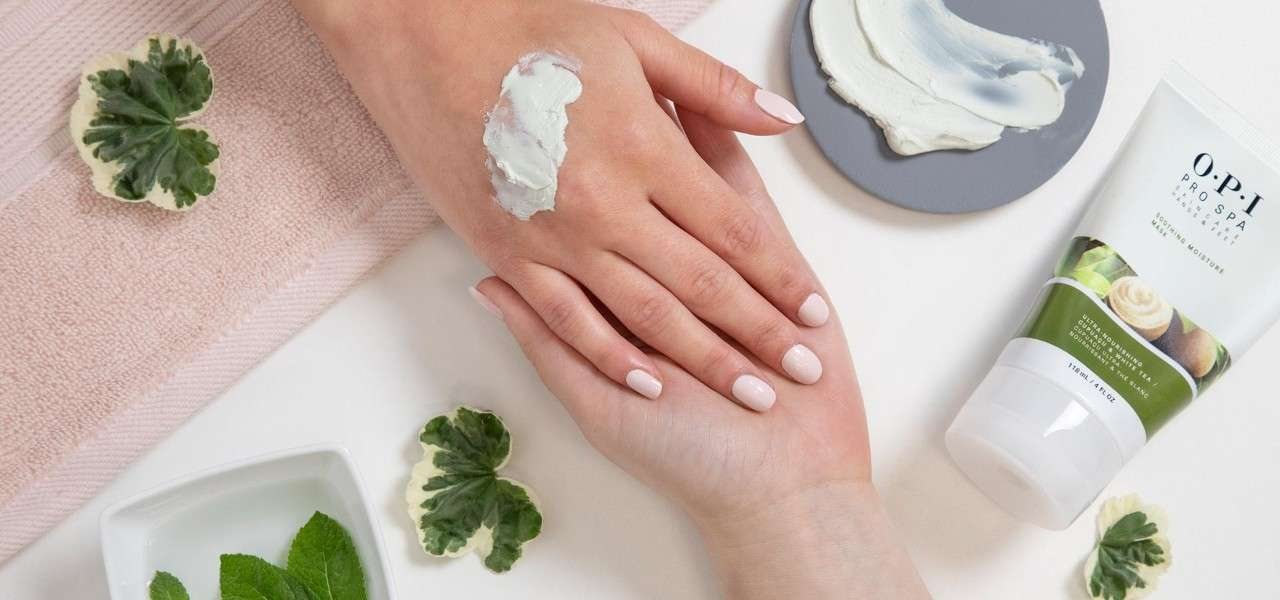 Hand receiving a manicure, OPI cream being used.