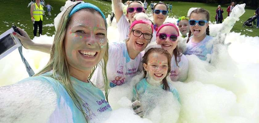 Group of staff at fundraising event covered in foam wearing matching Together for Short Lives charity t-shirts