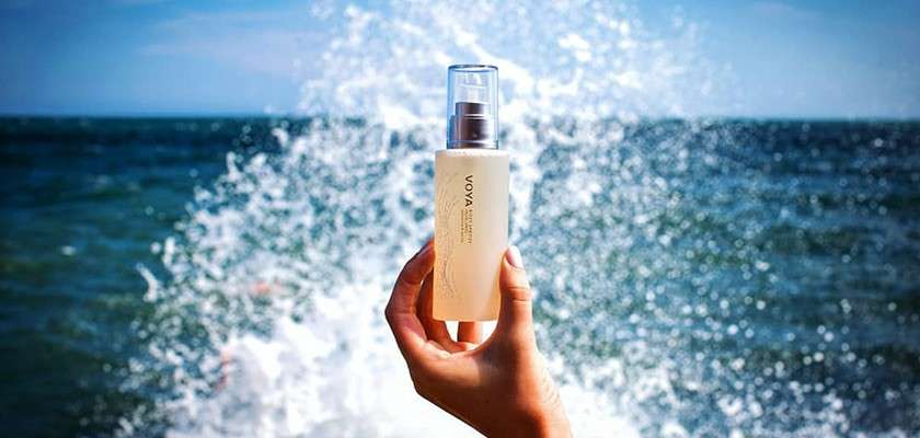Bottle of VOYA product being held up in front of sea wave