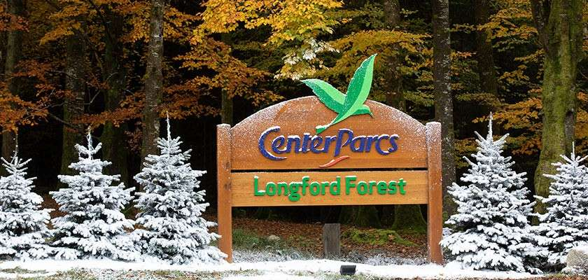 Longford Forest entrance sign surrounded by snowy Christmas trees