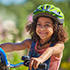 Young girl in green helmet on a cycle